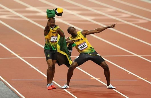 Usain Bolt, Yohan Blake, Michael Frater and Nesta Carter of Jamaica celebrate next to the clock after winning gold and setting a new world record of 36.84 during the Men's 4 x 100m Relay Final on Day 15 of the London 2012 Olympic Games at Olympic Stadium on August 11, 2012 in London, England.