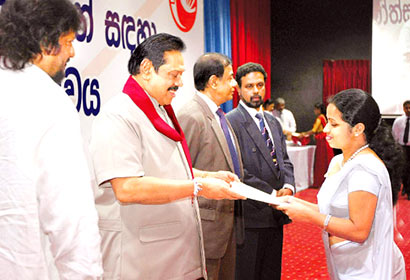 President Mahinda Rajapaksa presenting an appointment letter to a new recruit to the Sri Lanka Postal Service, at a ceremony at Temple Trees