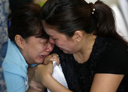 Family members of passengers onboard missing AirAsia flight QZ8501 cry at a waiting area in Juanda International Airport, Surabaya December 29, 2014