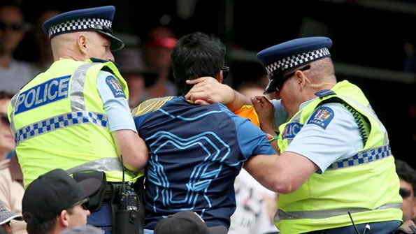 A Sri Lankan fan is removed from the Eden Park stands by police