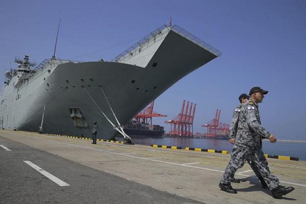 Australian naval officers walk past the HMAS Canberra