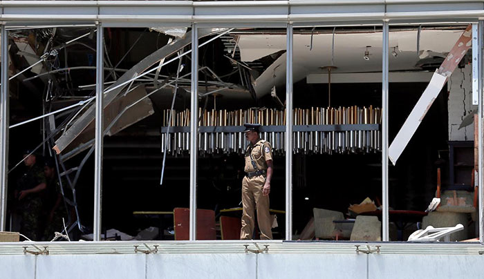 A police officer inspects the explosion area at Shangri-La hotel in Colombo Sri Lanka