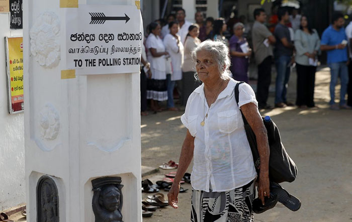Sri Lankan elderly woman leaves after casting her vote