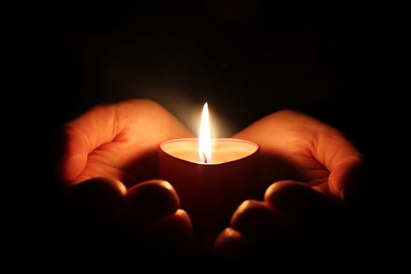 Candle on hand in dark
