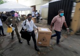 Sri Lankan police and election officials load ballot boxes in Colombo