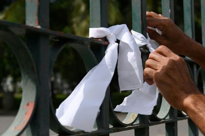 People tied white riboons on a cemetery fence in Colombo Sri Lanka to protest against the forced cremation of Coronavirus victims