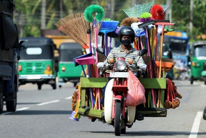 A street vendor selling houseware drives his motorcycle in Colombo, Sri Lanka