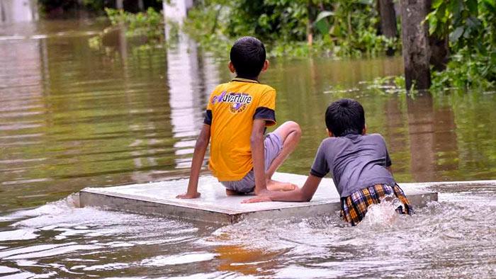 Children play on flooded roads in Gampaha, Sri Lanka