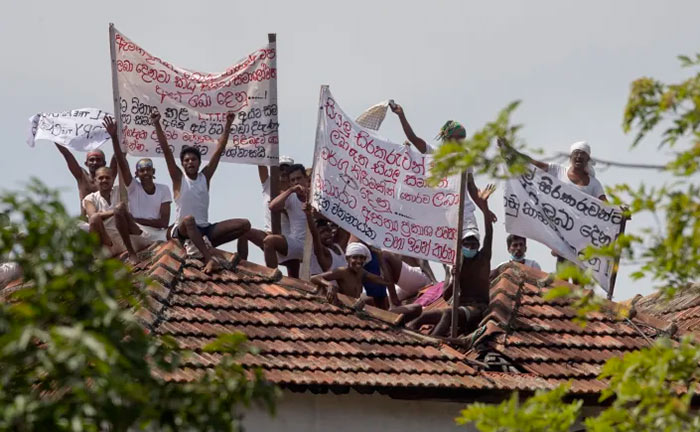 Death-row inmates of Sri Lanka's Welikada prison protest holding banners from the roof of the prison in Colombo, Sri Lanka