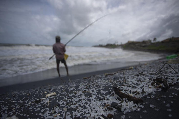 Sri Lankan man fishes on a polluted beach filled with plastic pellets