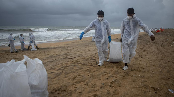 Sri Lankan Navy soldiers looking for plastic debris washed ashore from MV X-Press Pearl ship