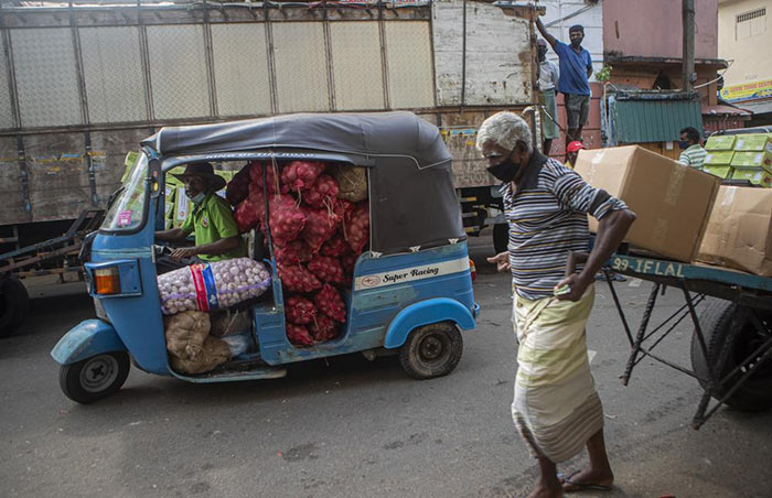 A Sri Lankan man transports a load of imported onions and garlic in an autorickshaw