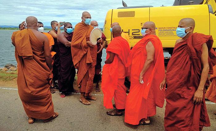 Buddhist monks stand against Parakrama Samudra walking path