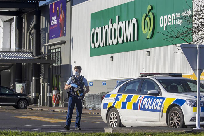 Armed police stand outside a supermarket in Auckland, New Zealand