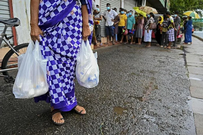 A woman carries food bags in Colombo Sri Lanka